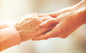 young woman hand holding with tenderness an elderly senior person hands